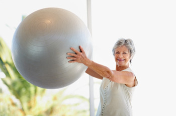 Image of a female older adult exercising with a gym ball.