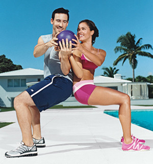 Image of a couple doing partner-type fitness training in an outdoor setting.