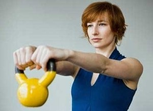 Image of a female client performing kettlebell moves as a fitness workout at home.