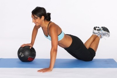 Image of a female client using a medicine ball in her fitness workout.