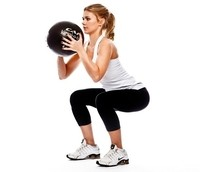 Image of lady client exercising with a medicine ball.