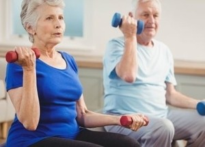 Image of an older couple working-out at home together.