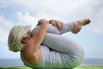 A female older adult performing a flexibility drill.