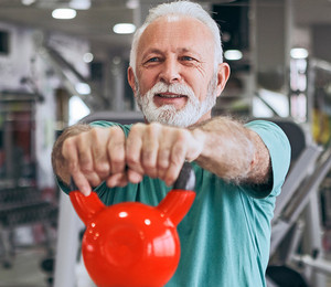 Image of a senior man exercising with a kettlebell.