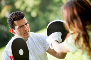 Photo of a fitness trainer working-out with his client outdoors.
