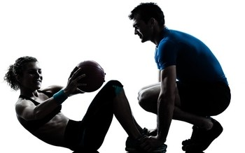 Image of a personal trainer working with a client.
