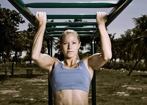 Image of a woman performing pull-ups as part of an outdoor fitness program.
